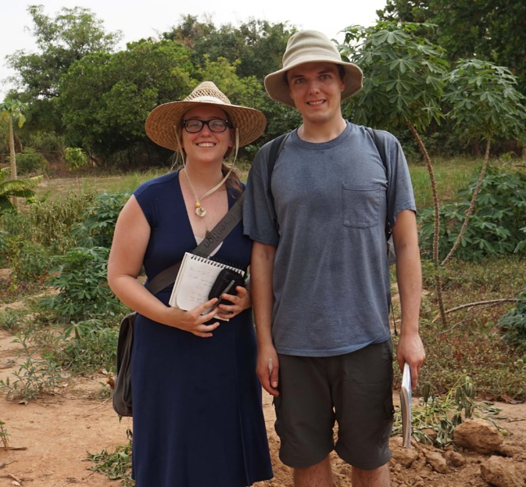 Molly and Chris at Ecova Mali. A papaya tree can be seen over Chriss' shoulder, and an eggplant by his knee.